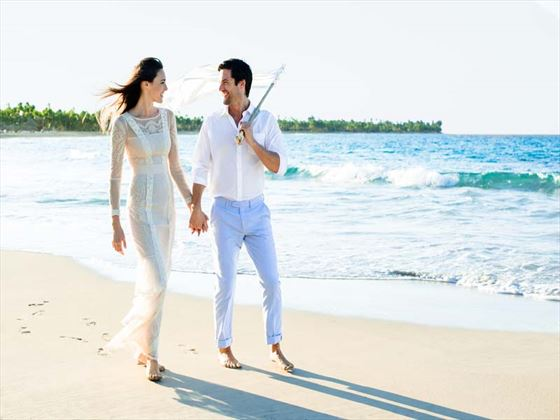 Bride & Groom strolling on the beach at Excellence Punta Cana