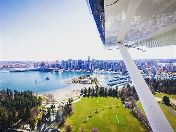 Seaplane flying over Stanley Park as it makes its descent to Coal Harbour